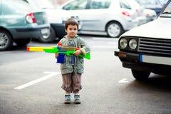 Boy holding toy rifle Stock Photos