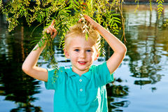 Boy Holding Tree Branches. A young, blond boy holds tree branches in front of a lake. He has blue eyes and is wearing a turquoise shirt Royalty Free Stock Image