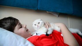 Boy holding a troublesome kitten on train. Boy holding a troublesome kitten on a train stock video footage