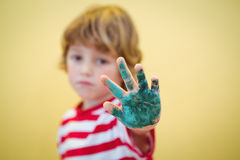 Boy holding up his paint covered hand Royalty Free Stock Images