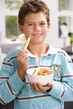 Boy (6-8) holding up piece of cucumber from bowl, smiling, portrait Stock Image