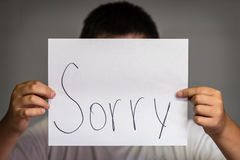 Boy Holding Up Sorry. A boy holding up a paper saying sorry Royalty Free Stock Photo