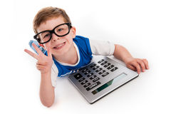 Boy Holding Up Three Fingers and a Big Calculator. Toddler boy lying on the floor with a big calculator and holding up three fingers Stock Image