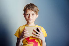 The boy is holding virtual reality googles, VR, blue background Stock Images