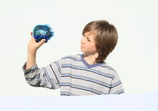 Boy holding and watching saving pig full of money Stock Images