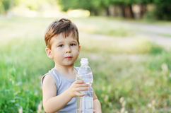 Boy holding a water bottle. Cute little boy holding a water bottle in summer park Royalty Free Stock Photo
