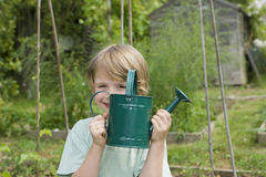 Boy Holding Watering Can In Garden Royalty Free Stock Photos