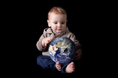 Boy holding world. Toddler boy holding world in his lap. Isolated on black Royalty Free Stock Photos