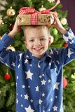 Boy Holding Wrapped Present In Front Of Tree Royalty Free Stock Photos