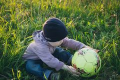 Boy with ball on the field with green grass royalty free stock images