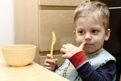 Boy holding yellow fork by small  brow bowl. In the kitchen Royalty Free Stock Photos