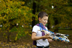 Boy holds airframe. Portrait of a pretty brunette little Boy holds plastic model airplane in autumn park Royalty Free Stock Photography