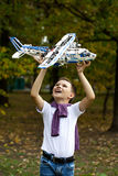 Boy holds airframe. Portrait of a pretty brunette little Boy holds plastic model airplane in autumn park Royalty Free Stock Image