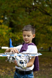 Boy holds airframe. Portrait of a pretty brunette little Boy holds plastic model airplane in autumn park Stock Photos