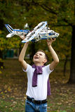 Boy holds airframe. Portrait of a pretty brunette little Boy holds plastic model airplane in autumn park Stock Image