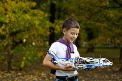 Boy holds airframe. Portrait of a pretty brunette little Boy holds plastic model airplane in autumn park Stock Photo