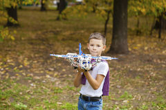 Boy holds airframe. Portrait of a pretty brunette little Boy holds plastic model airplane in autumn park Stock Images