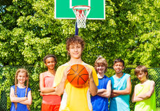 Boy holds ball and his friends standing behind Royalty Free Stock Photography