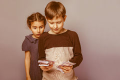 Boy holds banknotes money in the hands of the. Surprised girl opened her mouth on a gray background retro Stock Images
