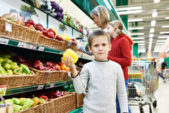 Boy holds bell pepper in supermarket Stock Images