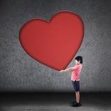 Boy holds big blank heart sign Stock Photo
