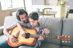 Boy holds big and brown guitar and trying to play. His dad is sitting behind him and help. They are practicing in. Playing this instrument royalty free stock photo
