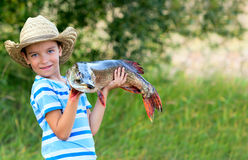 Boy holds big fish. Boy holds big pike he just caught stock photo