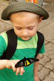 The boy holds a black butterfly Stock Images
