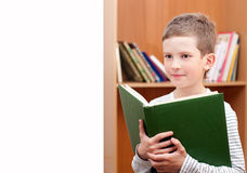 Boy holds book against bookshelf Stock Photography