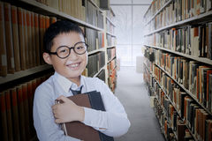 Boy holds book in the library aisle. Cute little boy smiling at the camera while holding a book in the library aisle Royalty Free Stock Photos