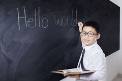 Boy holds book and writes Hello World Stock Image