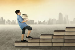 Boy holds books and walk on books stair Stock Images