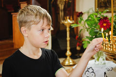 Boy holds a candle in church Royalty Free Stock Image