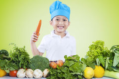 Boy holds carrot while preparing vegetables Stock Photo