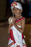 A boy holds a cowrie shell whilst participating in the Esala Perahera in Kandy in Sri Lanka. Stock Photography