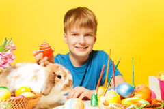 Boy holds Easter egg with cute rabbit on table Stock Image