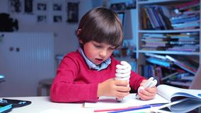 Boy holds fluorescent bulbs in his hands