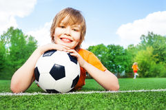 Boy holds football with bending in elbows arms Royalty Free Stock Photos