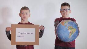 Boy holds a globe, a model of the planet Earth. Child is holding a sign with the inscription: TOGETHER WE ARE STRONGER