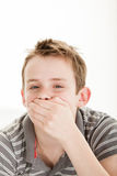 Boy holds hand over his mouth stifling laughter Royalty Free Stock Photos