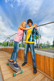 Boy holds hands of girl, teaches riding skateboard Royalty Free Stock Photography