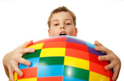 Boy holds before itself big inflatable ball. Boy holds before itself big inflatable multi-coloured ball, having captured his hands. Isolated on white background stock image