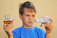 Boy holds model of sailing ship and ship in bottle Stock Photos