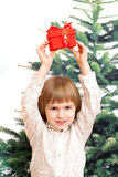 The boy holds a New Year's gift over the head Royalty Free Stock Image