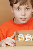 Boy holds open box of corrugated cardboard with cookies Royalty Free Stock Photos