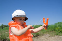 Boy holds an orange slingshot Stock Photos