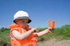 Boy holds an orange slingshot Stock Photos