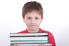 The boy holds a pile of books Stock Images
