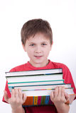 The boy holds a pile of books. To it it is heavy Royalty Free Stock Images