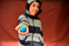 The boy holds the planet earth in his hands, on a red background. stock photos